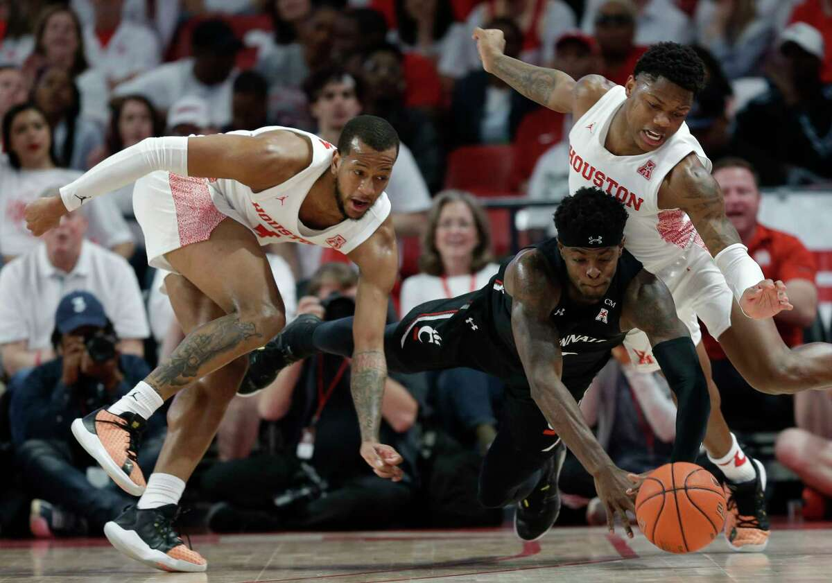 Cincinnati forward Tre Scott, center, Houston forward Justin Gorham, left, and guard Marcus Sasser, right, chase a loose ball during the first half of an NCAA college basketball game, Sunday, March 1, 2020, in Houston.