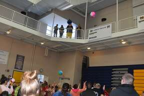 Carnival volunteers and mascot Chip toss prizes over the railing above the gymnasium to students who had outstretched arms trying to collect the prizes.