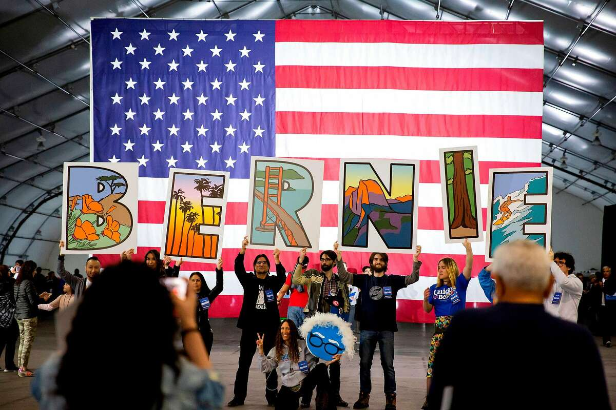 Supporters hold up signs in front of an American flag during a Presidential election rally for Democratic White House hopeful Vermont Senator Bernie Sanders in San Jose, California on March 1, 2020. (Photo by Brittany Hosea-Small / AFP) (Photo by BRITTANY HOSEA-SMALL/AFP via Getty Images)