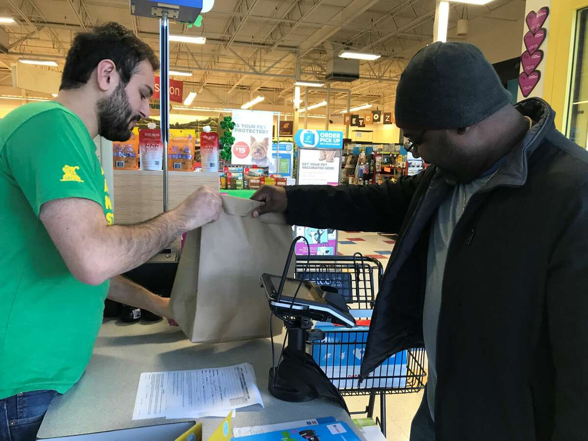 Petco manager Chris Milazzo at the Central Avenue Colonie store hands customer Claude Parlemont his items in a paper bag on the morning a plastic bag ban went into effect in New York, March 1, 2020.
