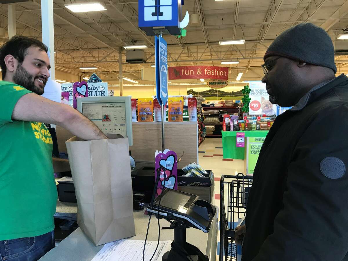 Petco manager Chris Milazzo at the Central Avenue Colonie store speaks with customer Claude Parlemont as he puts items in a paper bag on the morning a plastic bag ban went into effect in New York, March 1, 2020.