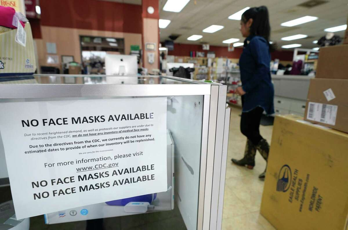 A no face masks sign is shown at the front counter as Meli Jimenez, sales manager, works at Spring Branch Medical Supply, 8700 Long Point Road., Friday, Feb. 28, 2020, in Houston. The store normally has four shelves of several types of face masks. Other items have been placed on the shelves since the store has been out of face masks for weeks.