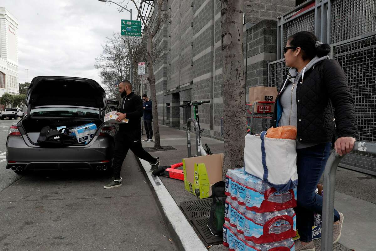 Ruby Trejo, right, watches as Aram Barnett loads his groceries and supplies into his car as she waits for a taxi in front of Costco where customers stocked up on supplies as worries over the Covid-19 virus in San Francisco, Calif., on Sunday, March 1, 2020. Stores around the Bay Area are seeing some items sell out like canned goods and hand sanitizer and dry goods that can last longer in people's homes.