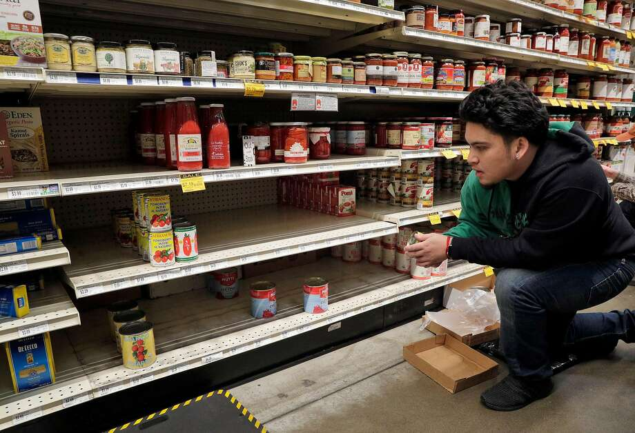 Zach Celso restocks shelves in the canned good section at Rainbow Grocery where customers stocked up on supplies as worries over the Covid-19 virus continued in San Francisco, Calif., on Sunday, March 1, 2020. Stores around the Bay Area are seeing some items sell out like canned goods and hand sanitizer and dry goods that can last longer in people's homes. Photo: Carlos Avila Gonzalez / The Chronicle