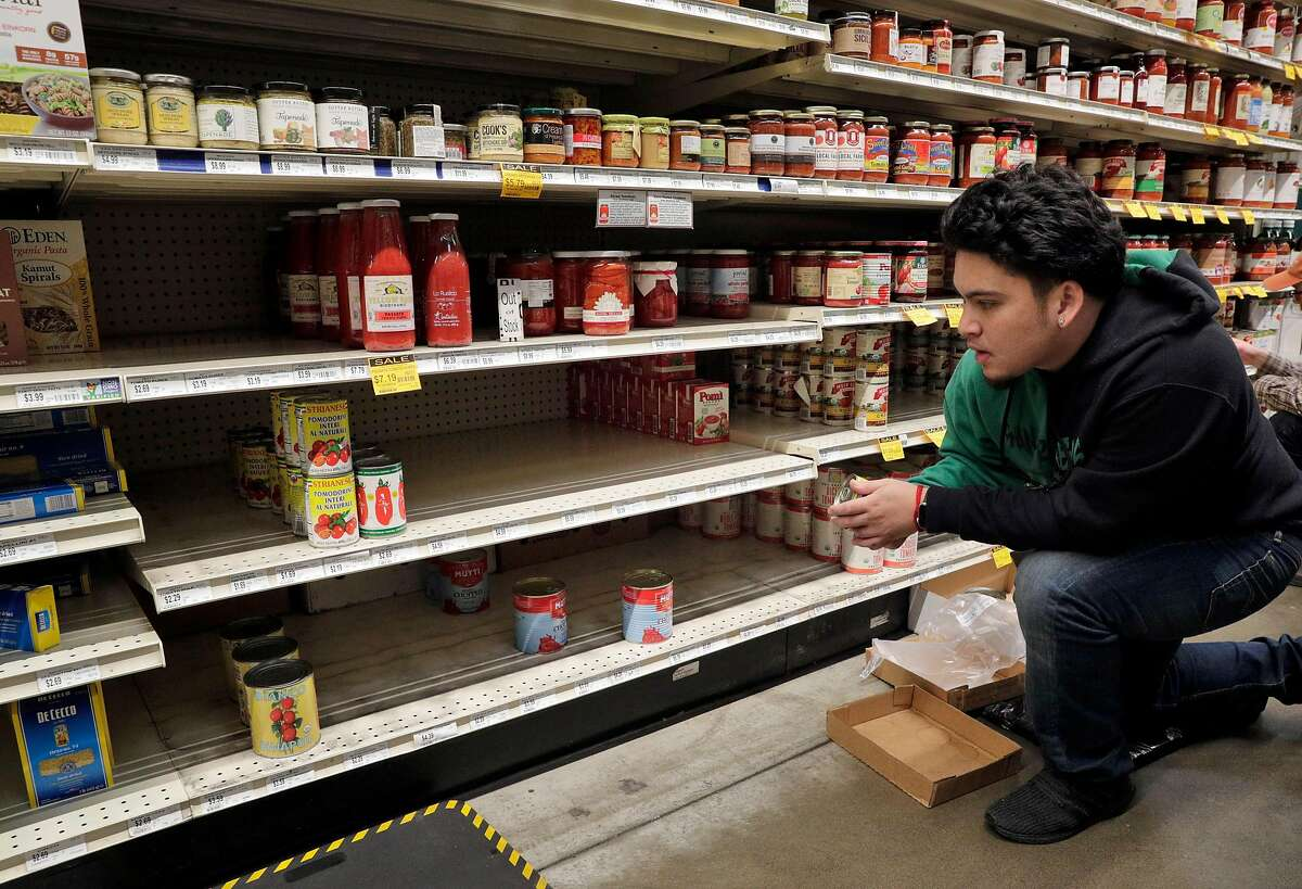 Zach Celso restocks shelves in the canned good section at Rainbow Grocery where customers stocked up on supplies as worries over the Covid-19 virus continued in San Francisco, Calif., on Sunday, March 1, 2020. Stores around the Bay Area are seeing some items sell out like canned goods and hand sanitizer and dry goods that can last longer in people's homes.