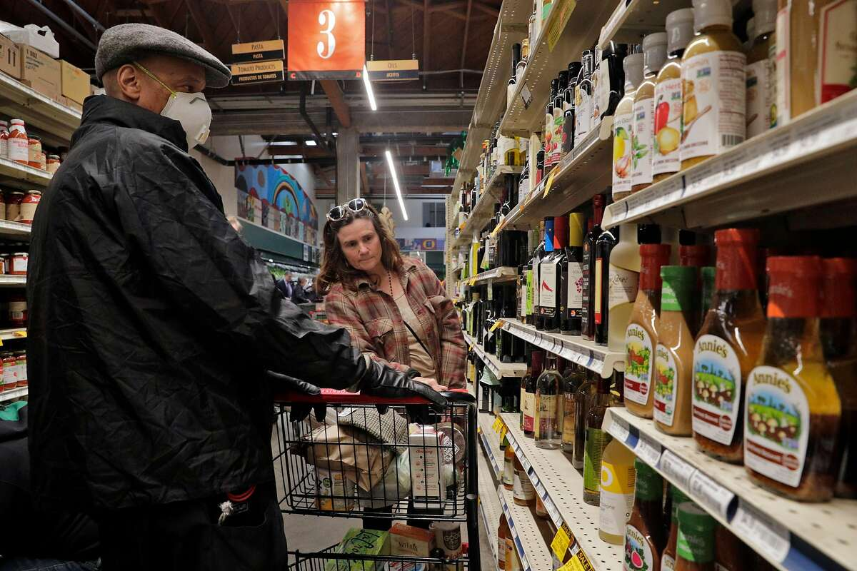 Customers (who declined to give their names) shop for vinegar at Rainbow Grocery where customers stocked up on supplies as worries over the Covid-19 virus in San Francisco, Calif., on Sunday, March 1, 2020. Stores around the Bay Area are seeing some items sell out like canned goods and hand sanitizer and dry goods that can last longer in people's homes.