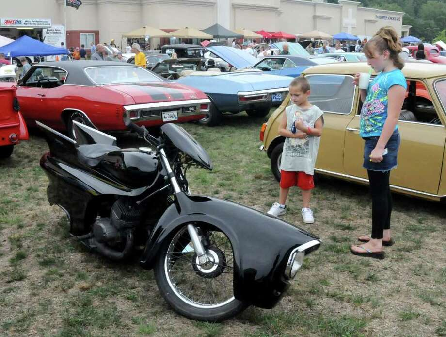 Joseph Woodward, 7, left, of Poughquag, N.Y., and Ashley Keeler, 12, of Wingdale, NY, take a look at a customized motorcycle at the 4th Annual Cruzin New Milford 2010 Car and Motorcycle Night on Sunday Aug. 15, 2010 at Faith Church in New Milford. Photo: Lisa Weir / The News-Times Freelance