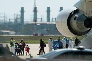 In this Feb 7, 2020, photo, evacuees from Wuhan, China, arrive via a chartered Boeing 747 at Joint Base San Antonio-Lackland. One of those evacuees, who later turned up positive for the coronavirus, was released from quarantine over the weekend after testing negative, but was returned to quarantine Sunday after testing positive again.
