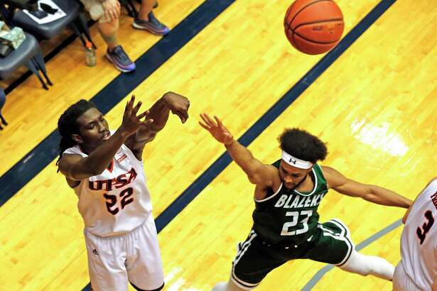 UTSA Keaton Wallace scores a three despite the pressure from UAB Jordan Brinson on Sunday, March 1, 2020 at the Convocation Center. UTSA defeated UAB 66-59.