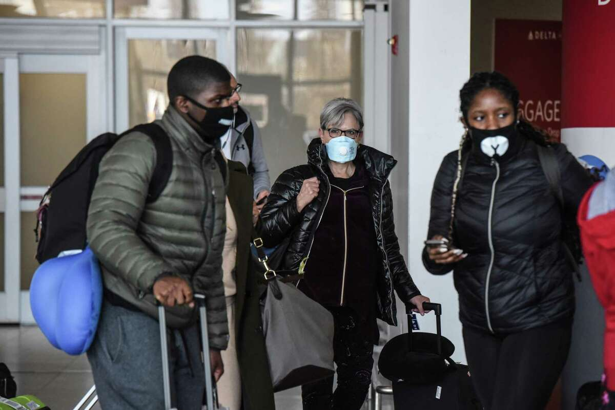 People wear masks at JFK Airport in New York, Feb. 27, 2020. The surgeon general urged the public to stop buying masks, warning that it won't help against the spread of the coronavirus but will take away important resources from health care professionals. (Stephanie Keith/The New York Times)