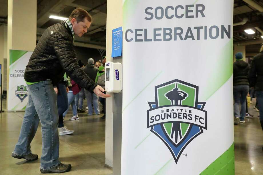 A man makes use of a hand-sanitizing station at CenturyLink Field prior to an MLS soccer match between the Seattle Sounders and the Chicago Fire, Sunday, March 1, 2020, in Seattle. Major North American professional sports leagues are talking to health officials and informing teams about the coronavirus outbreak. (AP Photo/Ted S. Warren) Photo: Ted S. Warren / Copyright 2020 The Associated Press. All rights reserved.