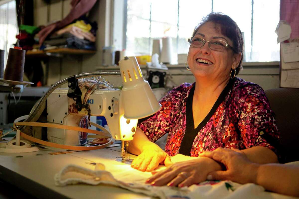 Lety Garza laughs from behind her sewing machine at Fuerza Unida. Garza is the head seamstress at the Thread of Justice, which offers a living wage to displaced garment workers and older women.