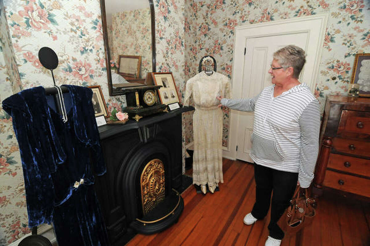 Margaret Kirbach, of Jerseyville, points to wedding dresses from her mother, right, and grandmother. The dresses were displayed as part of the Jersey County Historical Society's Tying the Knot: The History of Wedding Traditions event Saturday at the historical society's Cheney Mansion in Jerseyville.