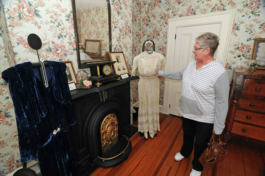 Margaret Kirbach, of Jerseyville, points to wedding dresses from her mother, right, and grandmother. The dresses were displayed as part of the Jersey County Historical Society's Tying the Knot: The History of Wedding Traditions event Saturday at the historical society's Cheney Mansion in Jerseyville. Photo: David Blanchette|For The Telegraph