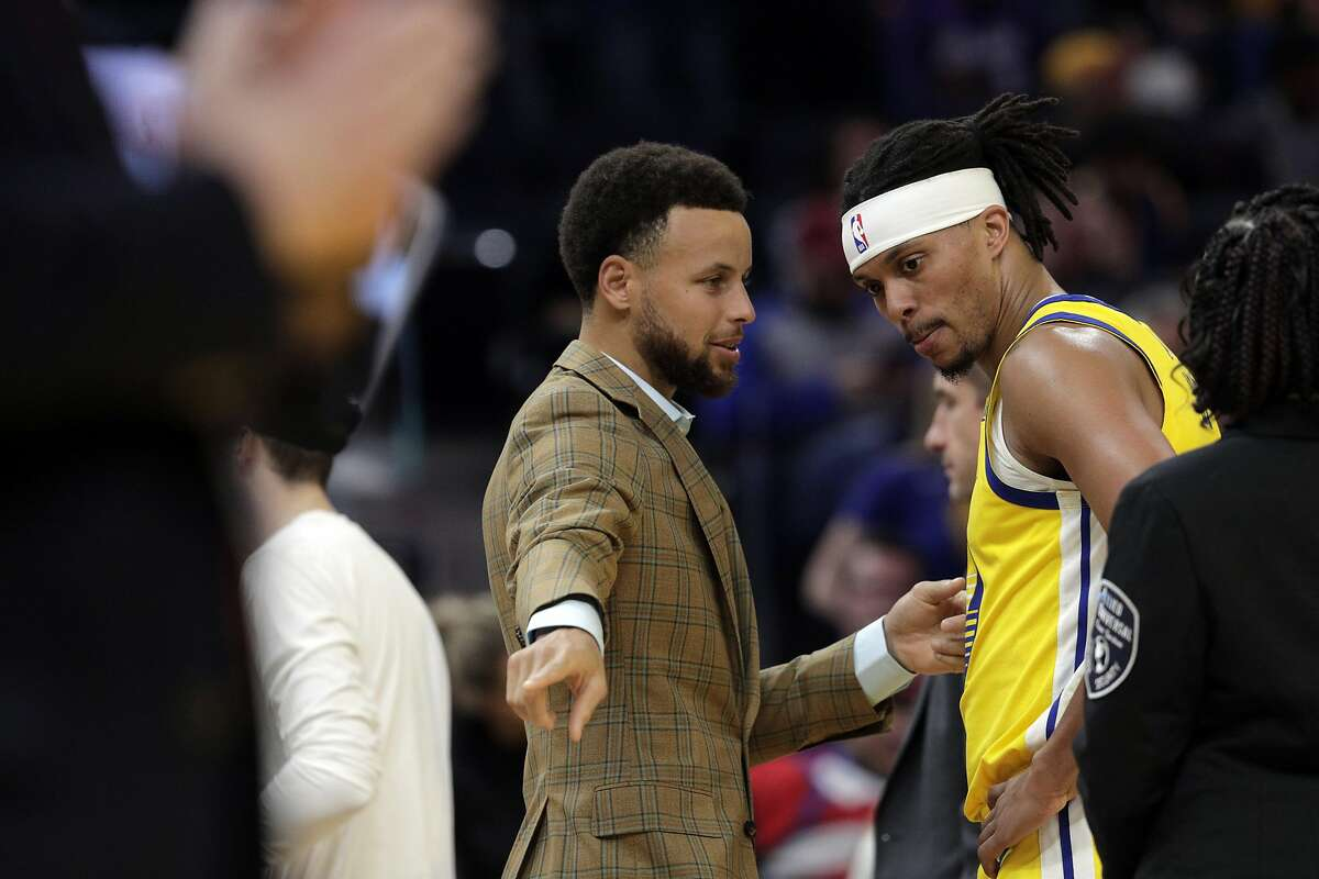 Stephen Curry (30) talks to Damion Lee (1) during a timeout in the first half as the Golden State Warriors played the Washington Wizards at Chase Center in San Francisco, Calif., on Sunday, March 1, 2020.