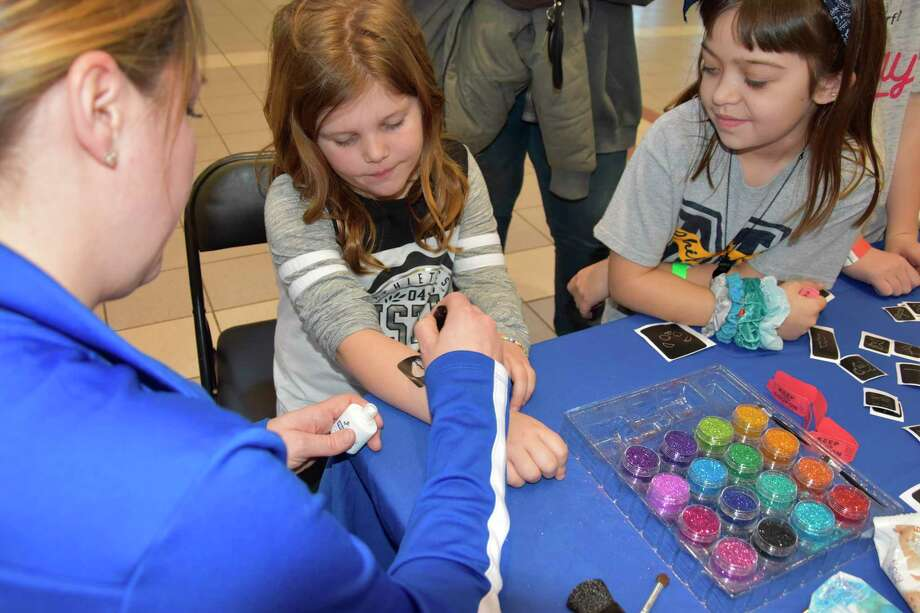 Marlee Hamilton (center) receives a glitter tattoo during the ATP Carnival Saturday afternoon. (Arielle Breen/News Advocate)