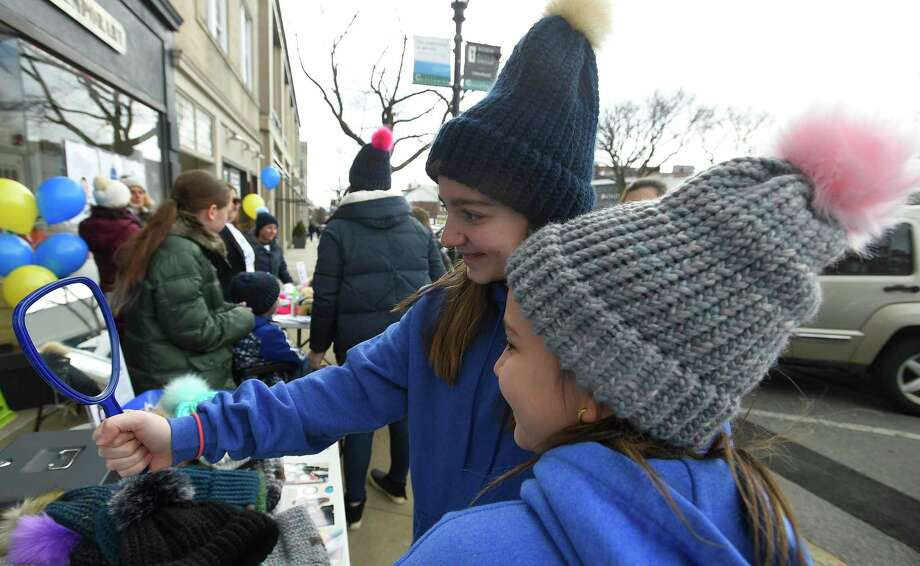 Candice Abitbol, 12, and her sister Celia Abitbol, 9, both of Greenwich, admire hats they purchased as part of the Best Day Ever project on Saturday. Glenville School teachers, students, families and community members set up shop on Greenwich Avenue and sold more than 500 hats, raising more than $9,000 to benefit the Vanishing White Matter Families Foundation. The project was started by Deirdre Burke, a Glenville teacher, to help one of her students, Sam Buck, who, despite living with VWM, sees every day as the Best Day Ever. Photo: Matthew Brown / Hearst Connecticut Media / Stamford Advocate