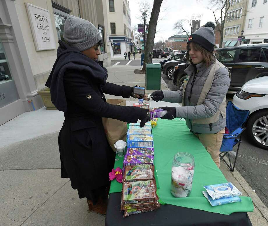 Stacy Westcarr, of Bridgeport, who works in the Greenwich area, stops to purchase some Girl Scout cookies from Sofia Adams and Tiffany Abrahams, both Cadet scouts from Troop 50397. The girls were selling the cookies along Greenwich Avenue in Greenwich on Saturday. Greenwich Girls Scouts are kicking off cookie booth sales this week. Troops will be selling their iconic cookies at various locations around Greenwich for the month of March. Troops will also be collecting donations for Cookies for Heroes, which sends cookies to servicemen and women in the military as well as veterans. Photo: Matthew Brown / Hearst Connecticut Media / Stamford Advocate