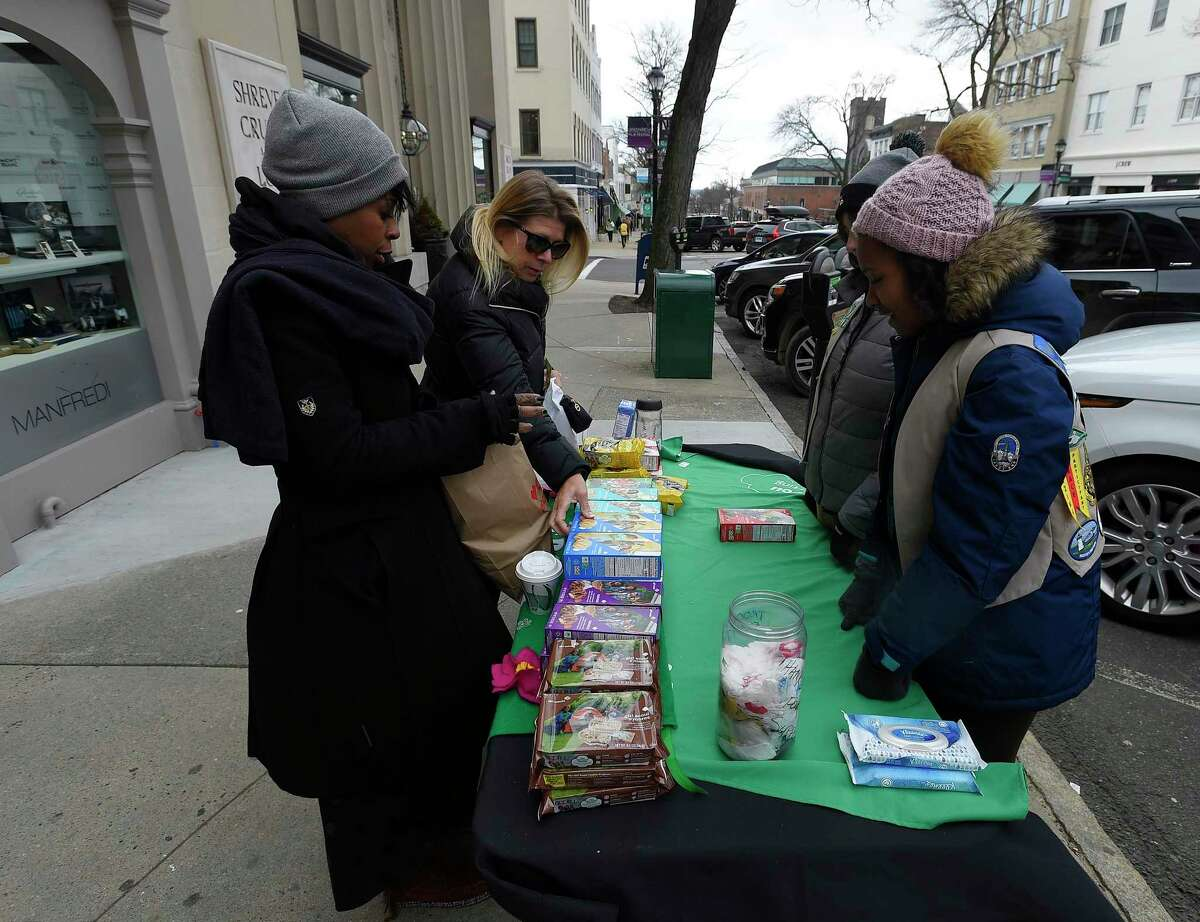 Stacy Westcarr of Bridgeport, who works in the Greenwich area, stops to purchase some Girl Scout cookies from Sofia Adams and Tiffany Abrahams, both Cadet scouts from Troop 50397. The girls were selling the iconic cookies along Greenwich Avenue in Greenwich, Conn., Saturday, Feb. 29, 2020. Greenwich Girls Scouts are kicking off cookie booth sales this week. Troops will be selling their iconic cookies at various locations around Greenwich for the month of March. Troops will also be collecting donations for Cookies for Heroes which sends cookies to servicemen and women in the US Military as well as veterans.