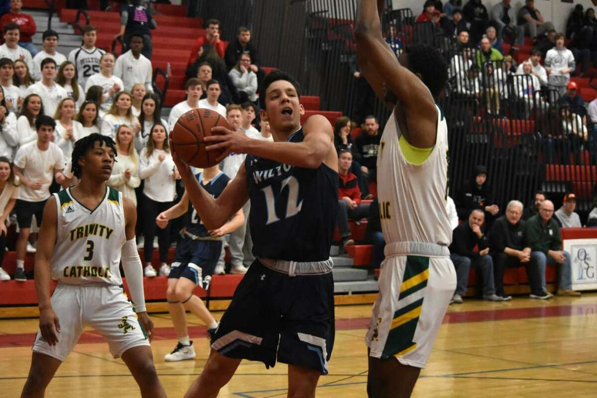 Wilton's Parker Woodring drives to the basket during the FCIAC quarterfinals against Trinity Catholic at Fairfield Warde on Saturday.