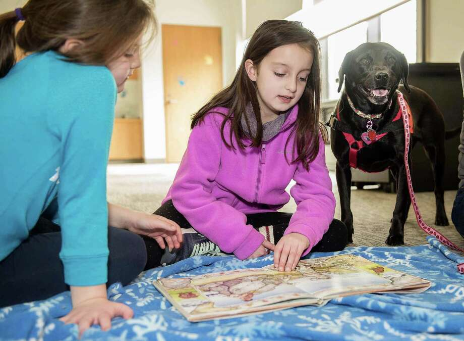 "Gabby, 7, and Olivia, 9, Baxendale of Wilton read ""Annie and the Wild Animals"" to Pepper, a rescue therapy dog from ROAR, at The Wilton Library on Saturday as part of the Tales for Tails program. Gabby, 7, and Olivia, 9, Baxendale of Wilton read ""Annie and the Wild Animals"" to Pepper, a rescue therapy dog from ROAR, at The Wilton Library on Saturday as part of the Tales for Tails program. Photo: Bryan Haeffele / Hearst Connecticut Media / BryanHaeffele"