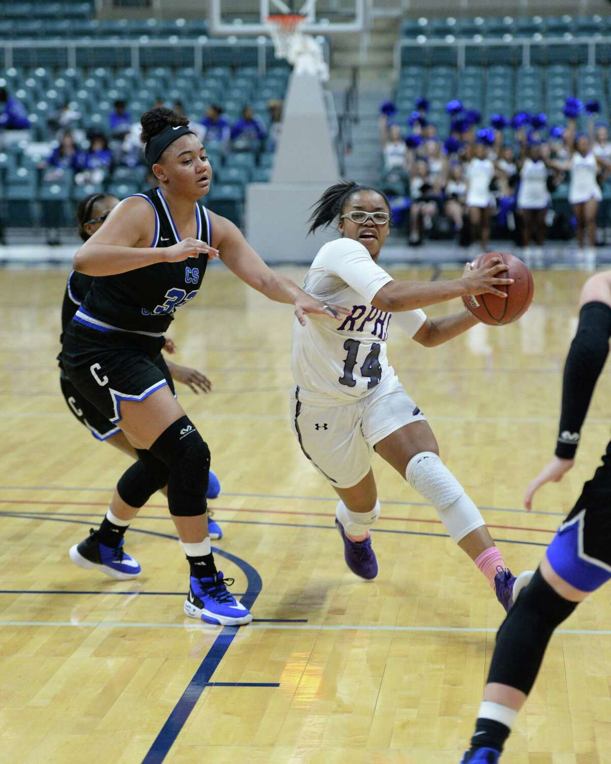 Aleighyah Fontenot (14) of Ridge Point drives past Blaise Blair (33) of Clear Springs during the second quarter of a Girls 6A Region III semifinal play-off game between the Ridge Point Panthers and the Clear Springs Chargers on Friday, February 28, 2020 at the Leonard Merrell Center, Katy, TX.