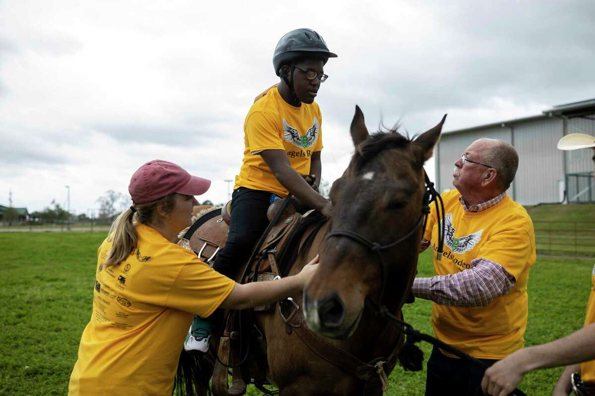 Elaijah Wilson, 15, hops onto a horse with the assistance of Clara Holt and Tom Holt during Angel's Rodeo at the Montgomery County Fairgrounds Equestrian Center, Sunday, March 1, 2020. Holts have been volunteers for the event for the last 4 years.