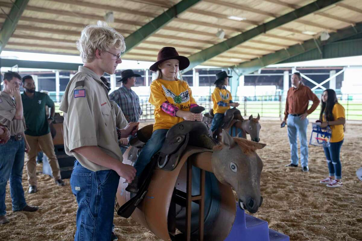 Aria Phelps, 5, rides a makeshift horse with the assistance of Boy Scouts of America troop 161 at the Montgomery County Fairgrounds Equestrian Center, Sunday, March 1, 2020. Angel's Rodeo held their annual rodeo fair for special need kids.