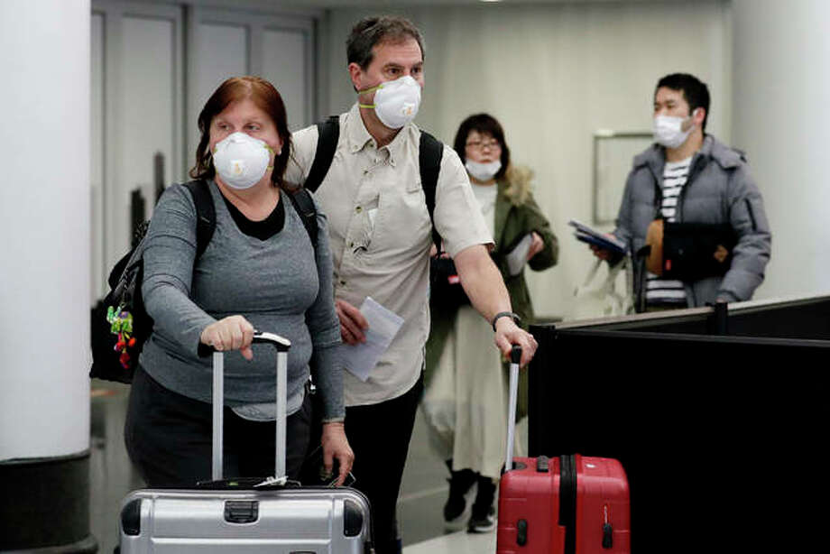 Travelers wear protective mask as they walk through Terminal 5 at O'Hare International Airport in Chicago on Sunday. The fourth case of the coronavirus in Illinois was reported Monday morning.
