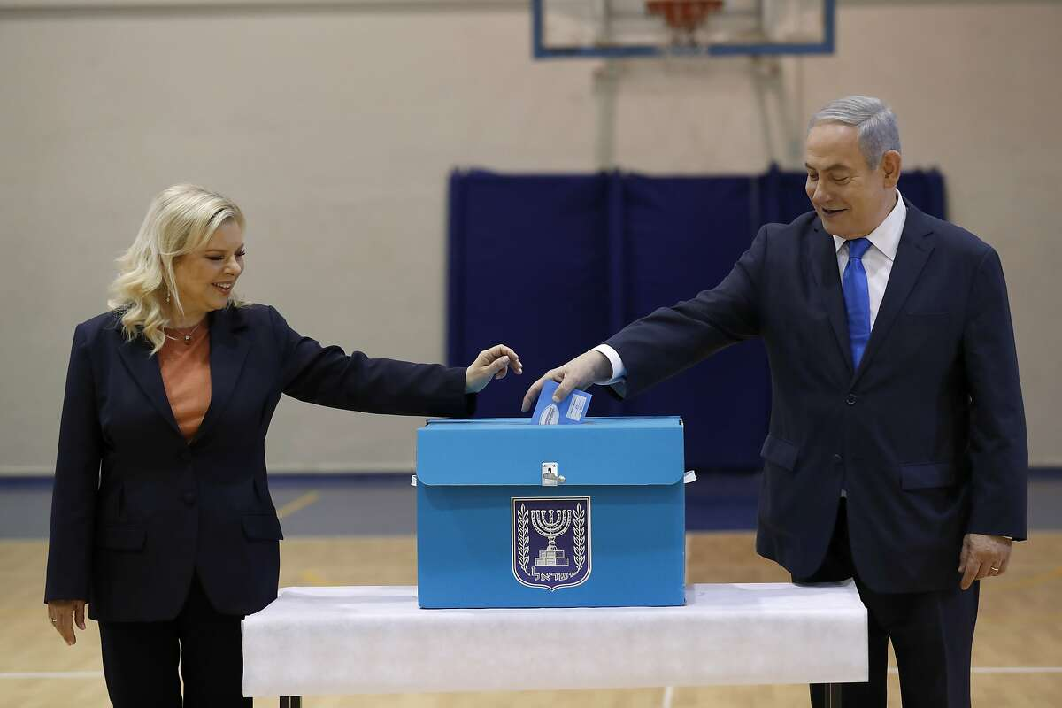 Israeli Prime Minister Benjamin Netanyahu and his wife Sara Netanyahu cast their ballots during the Israeli legislative elections at a polling station in Jerusalem, Monday, March 2, 2020. Israelis have begun voting in the country's unprecedented third election in less than a year. (Atef Safadi/Pool Photo via AP)