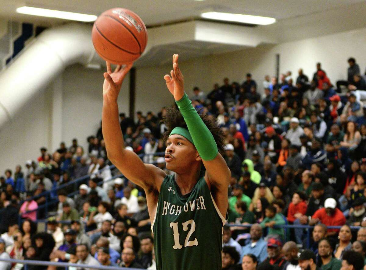 Bryce Griggs (12) of Hightower attempts a 3-point shot during the first half of a 5A Region III Bi-District playoff game between the Hightower Hurricanes and the Sharpstown Apollos on Monday, February 24, 2020 at Butler Fieldhouse, Houston, TX.