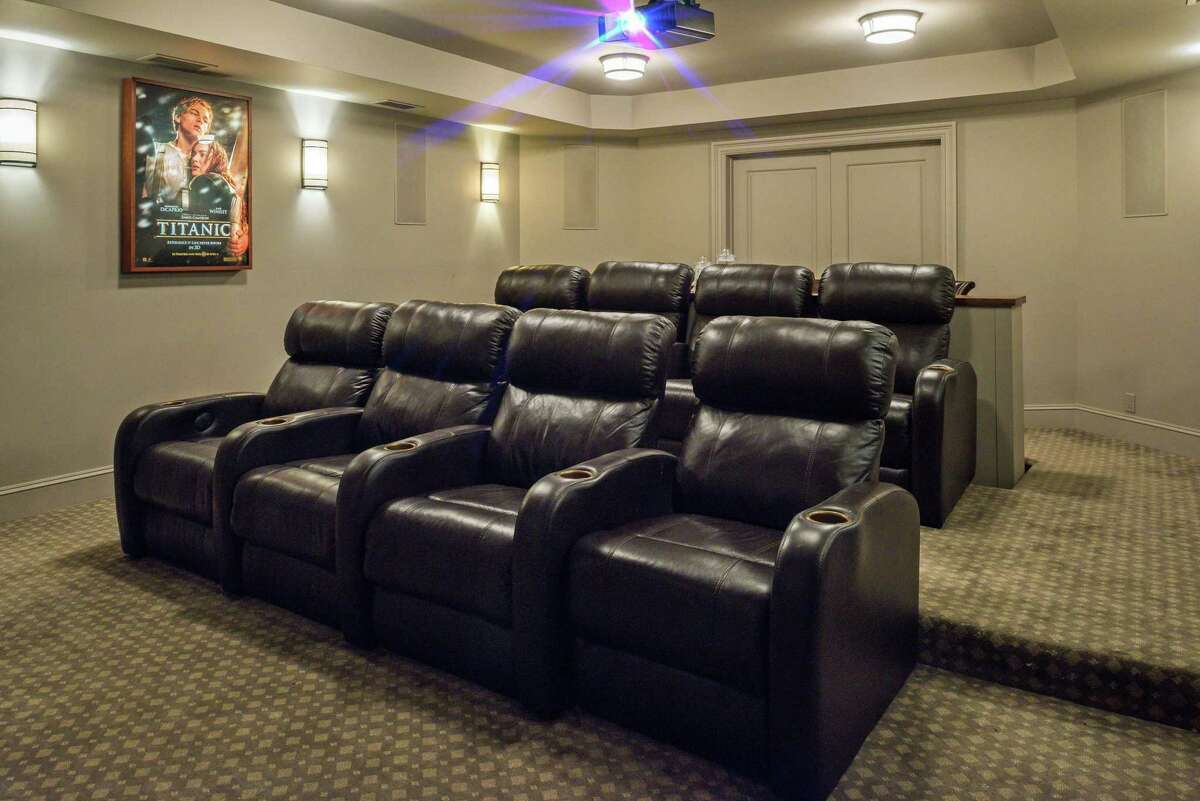 On the lower level there is a movie theater with a JVC projector to the 100-inch screen, surround sound speakers, tiered seating, and a snack bar with seating for four.