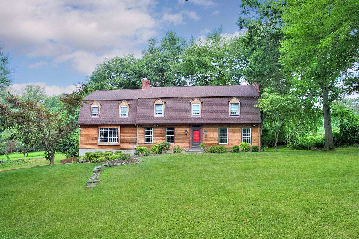 The colonial farmhouse with natural cedar clapboard at 21 High Acre Road sits on a corner lot not far from the Weston Historical Society.