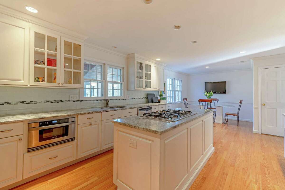 In the newly transformed eat-in-kitchen the features include custom cabinetry with up-lighting, a center island, granite counters, high-end appliances, built-in desk area, and a special custom-built indoor brick grill.