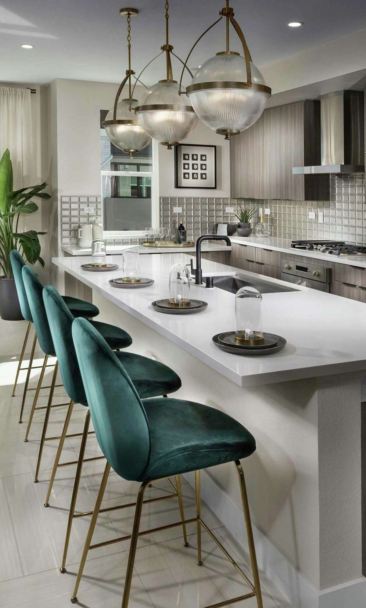 The open kitchen revolves around a bar island in this floor plan available in the