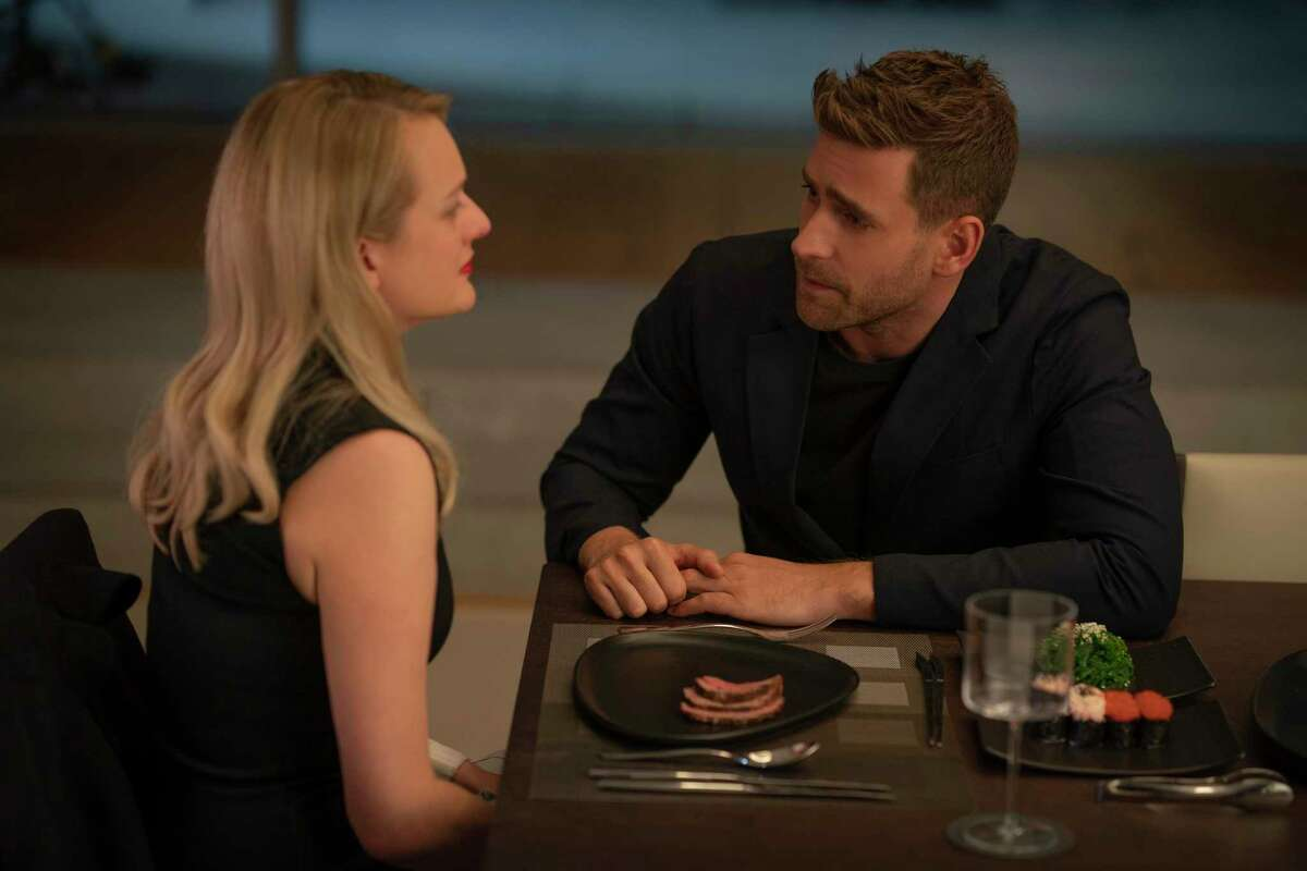 This image released by Universal Pictures shows Elisabeth Moss, left, and Oliver Jackson-Cohen in a scene from