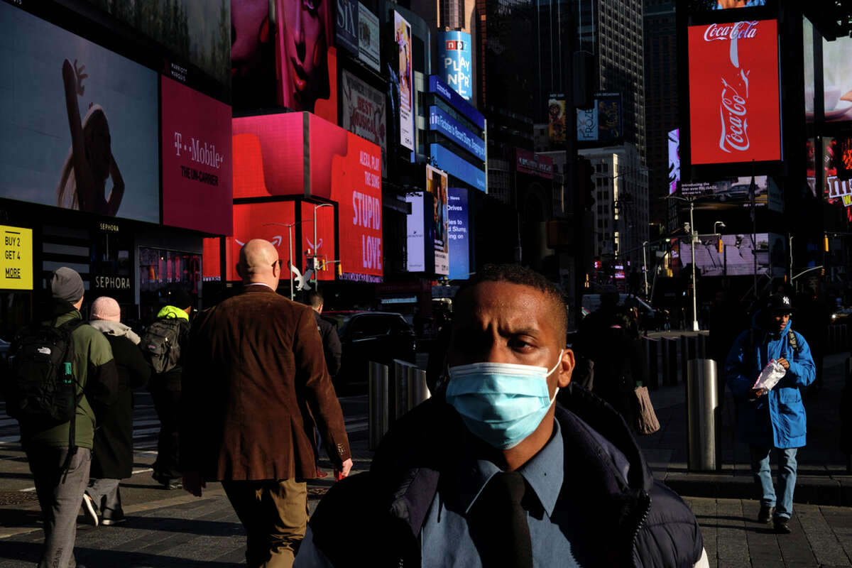 A man wears a face mask in New York's Times Square, Monday, March 2, 2020. New York officials warned on Monday that the coronavirus was likely to spread in New York City, a day after confirming that a Manhattan woman had contracted the virus while traveling in Iran and was now isolated in her home.