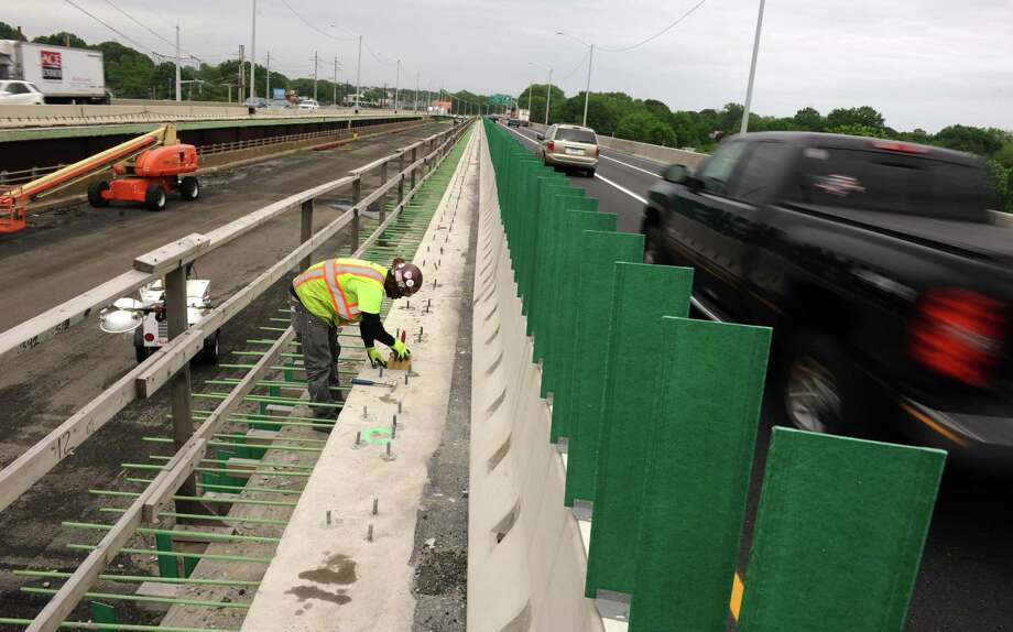 Edward Murphy, with Walsh Construction, levels off concrete as cars and trucks whiz past on I-95 while working on the Moses Wheeler Bridge between Milford and Stratford. Photo: File Photo / Connecticut Post