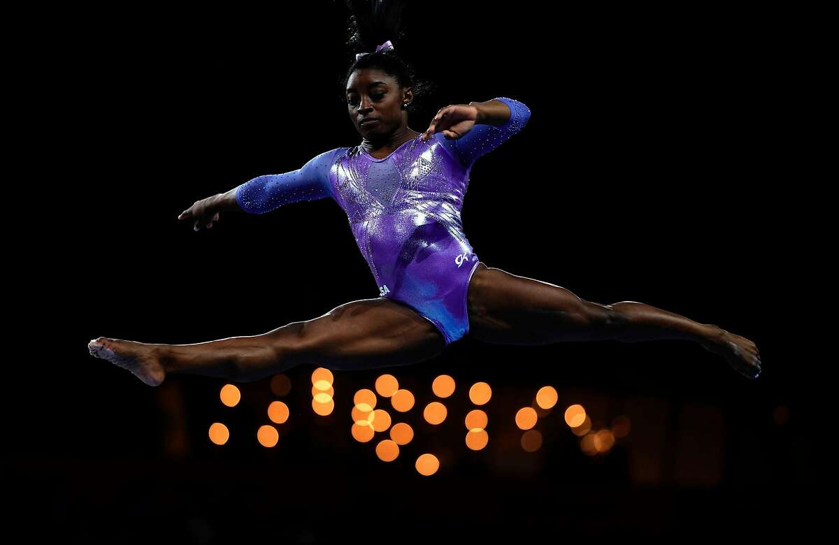 (FILES) In this file photo taken on October 13, 2019 USA's Simone Biles performs on the beam during the apparatus finals at the FIG Artistic Gymnastics World Championships at the Hanns-Martin-Schleyer-Halle in Stuttgart, southern Germany. - A proposed USA Gymnastics tiered settlement system would pay some sexual assault victims of former US team doctor Larry Nassar only $82,550, according to multiple reports February 22, 2020 detailing the payment plans. Simone Biles, expected to be among the stars of this year's Tokyo Olympics after winning four gold medals at Rio in 2016 and 19 world titles including a fifth all-around crown last year, would be among 66 gymnasts to receive the top-level settlement amount of $1.25 million. (Photo by Lionel BONAVENTURE / AFP) (Photo by LIONEL BONAVENTURE/AFP via Getty Images)