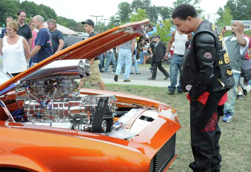 Kyle Smith of Bridgeport looks at a custom engine in a Charger at the 4th Annual Cruzin New Milford 2010 Car and Motorcycle Night on Sunday Aug. 15, 2010 at Faith Church in New Milford.