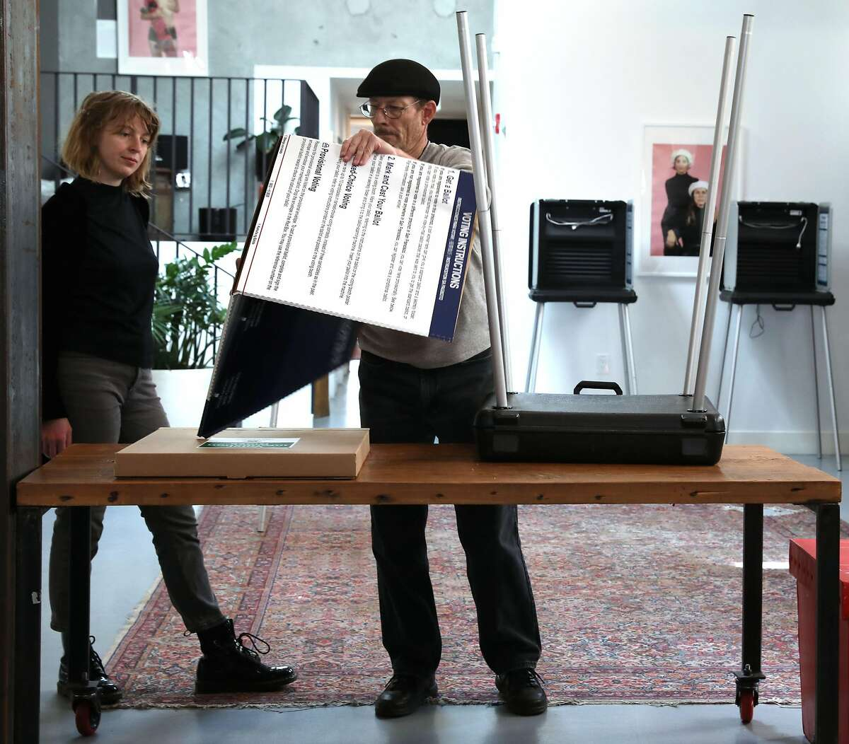 The Laundry manager Taylor Ovca (left) works with roving district support team supervisor Bill Delaney (middle) as he sets up a polling space at the coffee shop/gallery on Monday, March 2, 2020, in San Francisco, Calif.