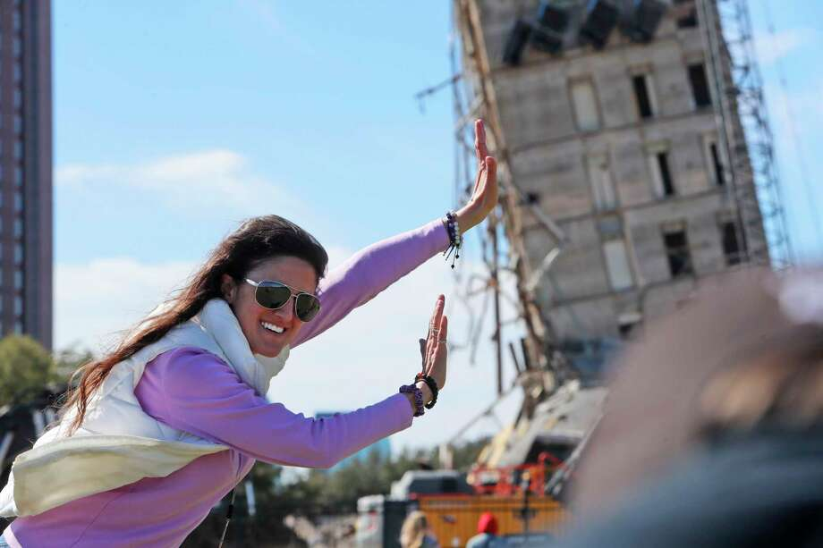 "Megan Dority poses for a photo with the so called ""Leaning Tower of Dallas"" as a crew works to topple the structure north of downtown Dallas, Monday, Feb. 24, 2020. The still standing structure is part of an 11-story building that found a second life online after surviving a first demolition attempt. The former Affiliated Computer Services building inspired jokes and comparisons to Italy's Leaning Tower of Pisa when a Feb. 16 implosion failed to bring down its core. The company that engineered the blast said some explosives did not go off. Photo: LM Otero, AP / Copyright 2020 The Associated Press. All rights reserved."