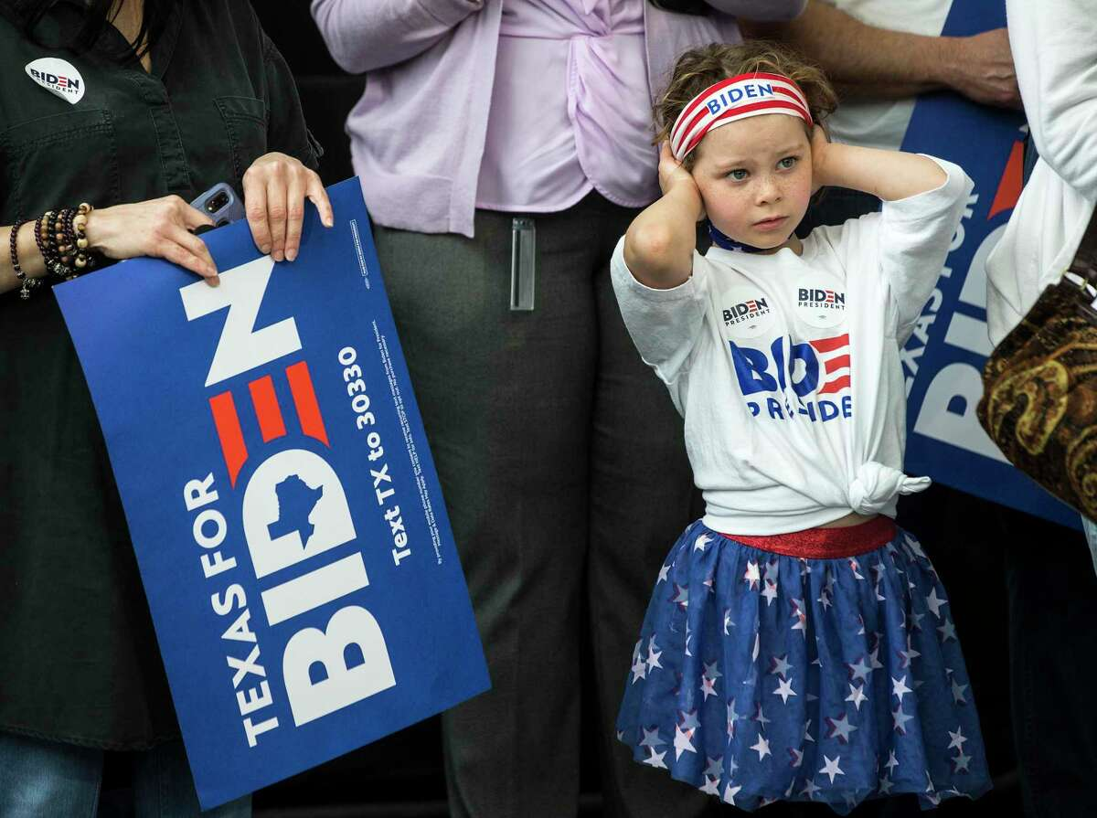 A young supporter of Democratic presidential hopeful former Vice President Joe Biden covers her ears as loud music is played before Biden's campaign speech on Monday, March 2, 2020 at Texas Southern University in Houston.