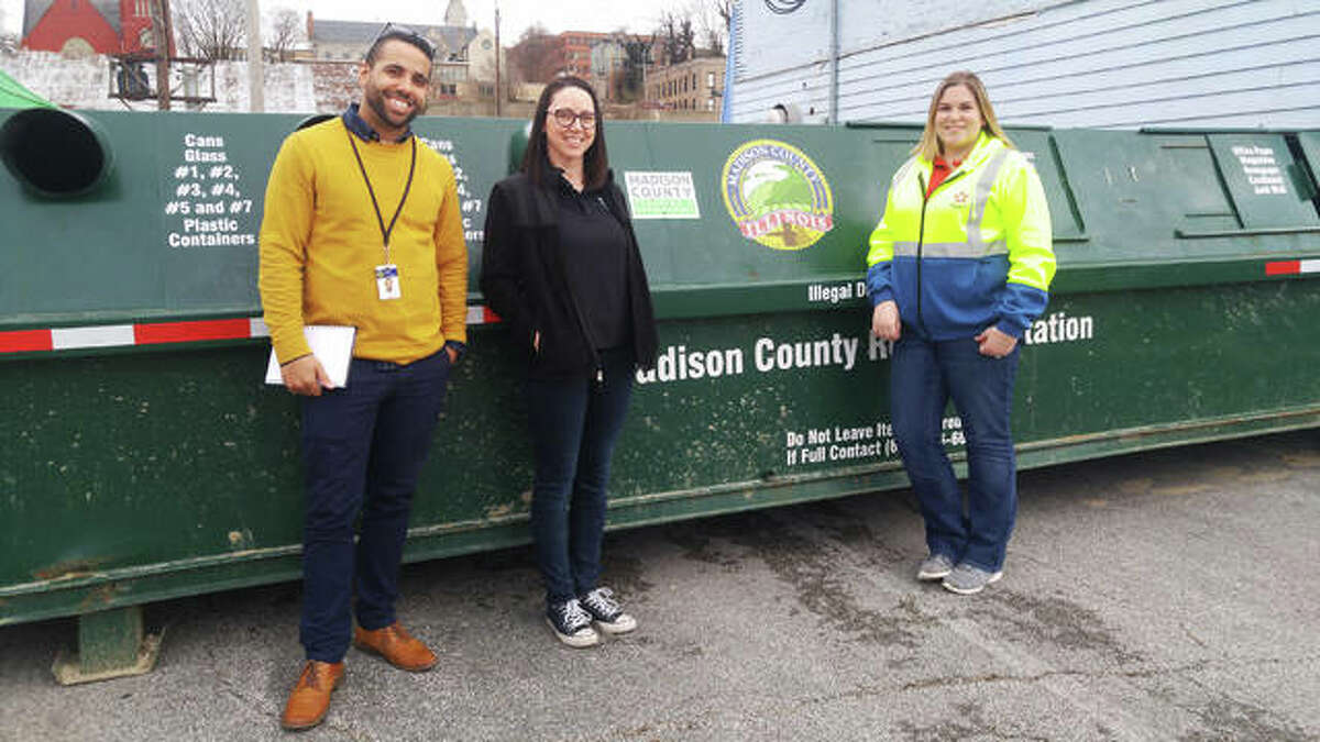 Madison County employees, from left, Brandon Banks and Andi Yancey, along with a representative of Republic Services, stand in front of Alton's new downtown recycling drop-off station at 410 Piasa St. behind the former Argosy building and Danny's Lounge. The station formerly was in the Lowe's parking lot on Homer Adams Parkway in Alton, but was absent for months while the county swought a new location.