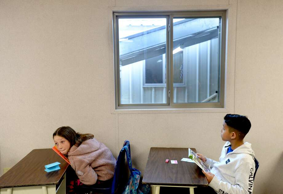 """Students complete a reading assignment in their new classroom as Hamshire-Fannett students and teachers get to know the newly-built portables on the first full day of classes for the elementary and intermediate students, who have been on half days since Imelda flooded the campuses in September. Intermediate School Principal Marla Gilmore said the orientation time to show the 300-plus 4th and 5th graders where teacher classrooms, the office and school nurse are is """"just your typical first day....in March."""" Monday's return to a full-day schedule marks the third """"first day"""" the students have had this year and the third campus they've had in one year's time. Photo taken Monday, March 2, 2020 Kim Brent/The Enterprise Photo: Kim Brent/The Enterprise"""