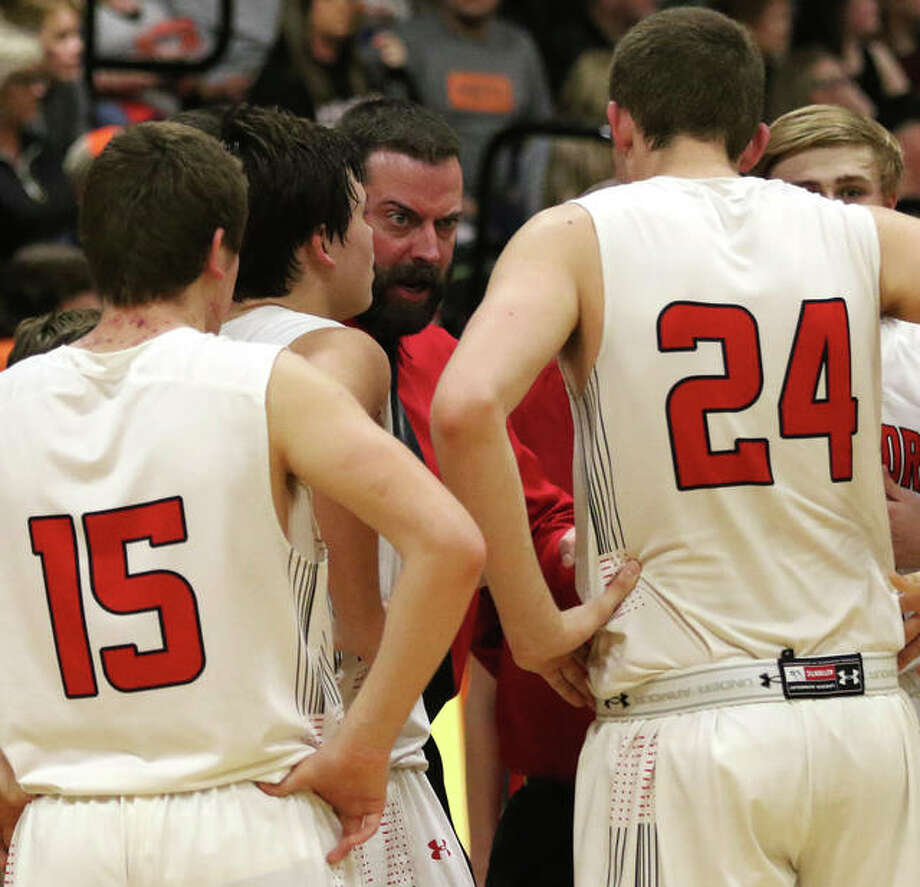 Calhoun coach Ryan Graner (middle) delivers his point to Ben Eberlin (24) during a timeout in the second half Friday night at the Raymond Class 1A Regional. Photo: Greg Shashack / The Telegraph