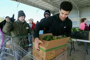 Kade Moss, 17, with Clemens High School's culinary arts program, loads a box of food into a basket at the mobile food pantry funded by Bracken United Methodist Church at Pickrell Park in Schertz on Wednesday.