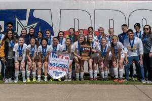 Members of the John Paul II Guardians soccer team pose with the banner proclaiming them as TAPPS Division 3 State Champions.