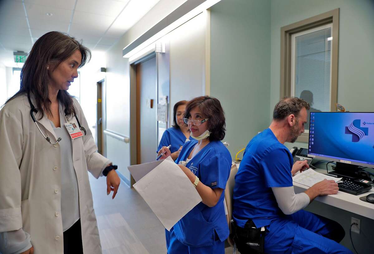 Dr. Wendy Zachary, left, checks in with nursing staff during a shift change where she is medical director of the Acute Care of the Elderly (ACE) unit at California Pacific Medical Center Mission Bernal campus in San Francisco, Calif., on Monday, March 2, 2020.
