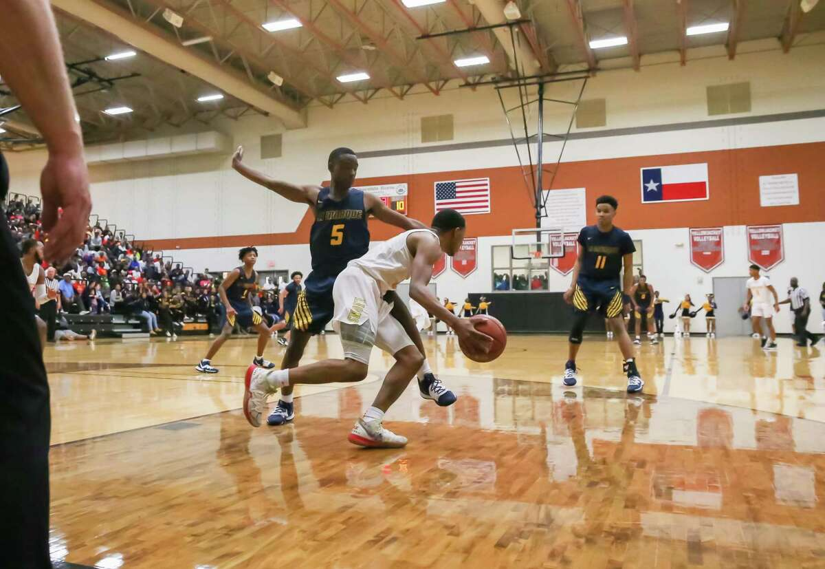 Yates Elijah Elliott (11) drives the ball past La Marque Frezno Bell (5) in the first quarter of the La Marque vs Yates boys' basketball Regional Quarter Final game on at Alvin High School Field House on March 2, 2020 in Alvin, TX.